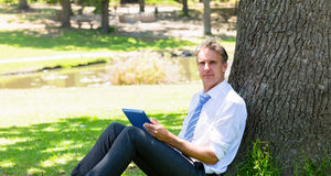 Homme d'affaires avec la tablette en parc Photographie stock libre de droits