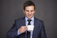 Homme d'affaires avec la tasse de café sur le gris Images stock