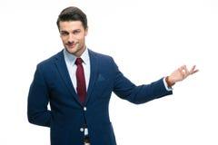 Homme d'affaires avec le bras à l'extérieur dans un geste de accueil Photos stock