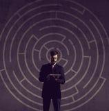 Homme d'affaires avec le comprimé d'ordinateur se tenant au-dessus du backgro de labyrinthe Photos stock