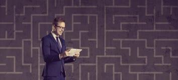 Homme d'affaires avec le comprimé d'ordinateur se tenant sur un backgro de labyrinthe Image stock