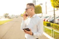 Homme d'affaires avec le comprimé de téléphone portable dans des mains Image stock