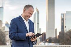 Homme d'affaires avec le comprimé devant des immeubles de bureaux Photo libre de droits