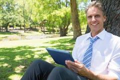 Homme d'affaires avec le comprimé numérique en parc Images libres de droits