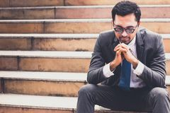 Homme d'affaires avec le costume se reposant à l'escalier dans la ville photo stock