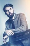 Homme d'affaires avec le coude placé sur la chaise de retour Photos libres de droits