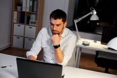 Homme d'affaires avec le fonctionnement d'ordinateur portable au bureau de nuit photographie stock