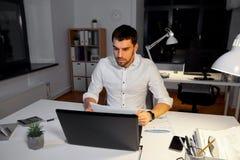 Homme d'affaires avec le fonctionnement d'ordinateur portable au bureau de nuit images stock