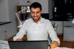 Homme d'affaires avec le fonctionnement d'ordinateur portable au bureau de nuit photos libres de droits