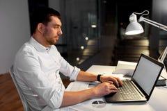 Homme d'affaires avec le fonctionnement d'ordinateur portable au bureau de nuit photo stock