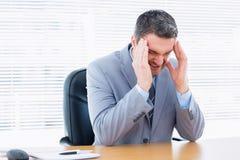 Homme d'affaires avec le mal de tête grave au bureau Image stock