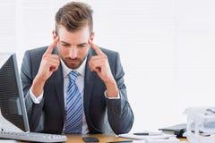 Homme d'affaires avec le mal de tête grave se reposant au bureau Photographie stock libre de droits
