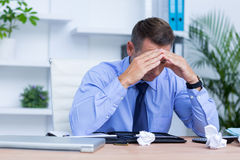 Homme d'affaires avec le mal de tête grave se reposant au bureau photo stock