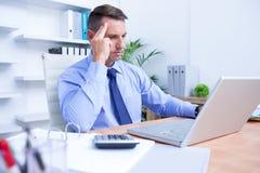 Homme d'affaires avec le mal de tête grave se reposant au bureau Photo libre de droits