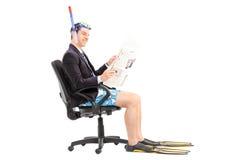 Homme d'affaires avec le masque de plongée lisant les actualités Photographie stock libre de droits
