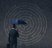 Homme d'affaires avec le parapluie se tenant au-dessus du fond de labyrinthe Bu Images libres de droits