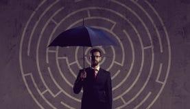 Homme d'affaires avec le parapluie se tenant au-dessus du fond de labyrinthe Bu Photographie stock