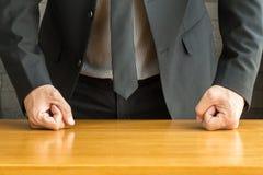 Homme d'affaires avec le poing serré sur le bureau image libre de droits