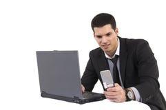 Homme d'affaires avec le premier ordinateur et le téléphone de genoux Photographie stock libre de droits