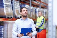 Homme d'affaires avec le presse-papiers à l'entrepôt Image stock