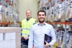 Homme d'affaires avec le presse-papiers au-dessus du chargeur d'entrepôt Photos libres de droits