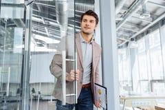 Homme d'affaires avec le presse-papiers présentant la porte dans le bureau Images stock