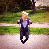 Homme d'affaires avec le sac de papier sur la tête dans l'oscillation Images stock