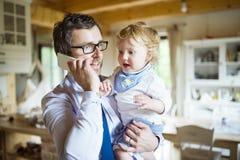 Homme d'affaires avec le smartphone à la maison avec le fils dans les bras Images libres de droits