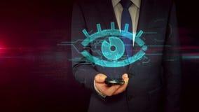 Homme d'affaires avec le smartphone et le concept de espionnage d'hologramme de signe d'oeil banque de vidéos
