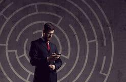 Homme d'affaires avec le smartphone se tenant au-dessus du fond de labyrinthe Photographie stock libre de droits