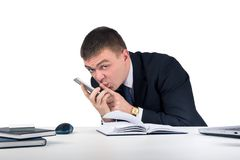 Homme d'affaires avec le smartphone tenant son doigt devant sa bouche et faisant le geste de silence Photographie stock libre de droits