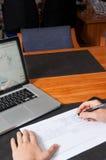 Homme d'affaires avec le stylo, les documents, et l'ordinateur portable Photographie stock