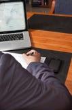 Homme d'affaires avec le stylo, les documents, l'ordinateur portable et le smartphone Photographie stock