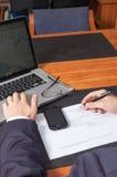 Homme d'affaires avec le stylo, les documents, l'ordinateur portable et le smartphone Photo stock