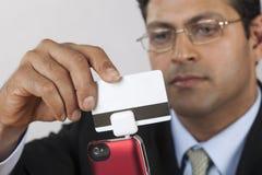 Homme d'affaires avec le swiper par la carte de crédit Photographie stock libre de droits