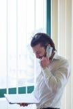 Homme d'affaires avec le téléphone devant la fenêtre Photographie stock libre de droits