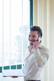 Homme d'affaires avec le téléphone devant la fenêtre Image stock