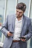 Homme d'affaires avec le téléphone et le portefeuille dans le secteur urbain Photographie stock