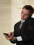 Homme d'affaires avec le téléphone parlant de calculatrice Photo libre de droits