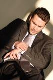 Homme d'affaires avec le téléphone regardant la montre Photos libres de droits