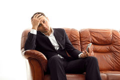 Homme d'affaires avec le téléphone sur le divan tenant la tête Image libre de droits