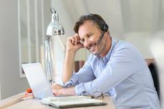 Homme d'affaires avec le télétravail de casque sur l'ordinateur portable photo stock