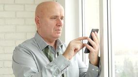 Homme d'affaires avec le texte non lié de lien utilisant le téléphone portable devant la fenêtre de bureau clips vidéos