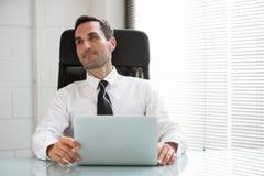 Homme d'affaires avec les écouteurs et l'ordinateur portable Photos stock