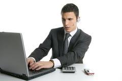 Homme d'affaires avec les écouteurs et l'ordinateur portatif Image libre de droits