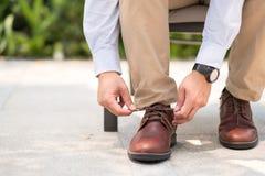 Homme d'affaires avec les chaussures en cuir attachant des dentelles de chaussure photos libres de droits