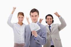 Homme d'affaires avec les collègues et l'argent encourageants Photo libre de droits