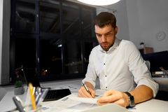 Homme d'affaires avec les papiers et l'ordinateur portable au bureau de nuit image stock