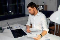 Homme d'affaires avec les papiers et l'ordinateur portable au bureau de nuit images stock