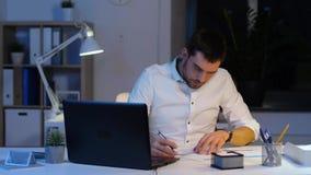 Homme d'affaires avec les papiers et l'ordinateur portable au bureau de nuit banque de vidéos